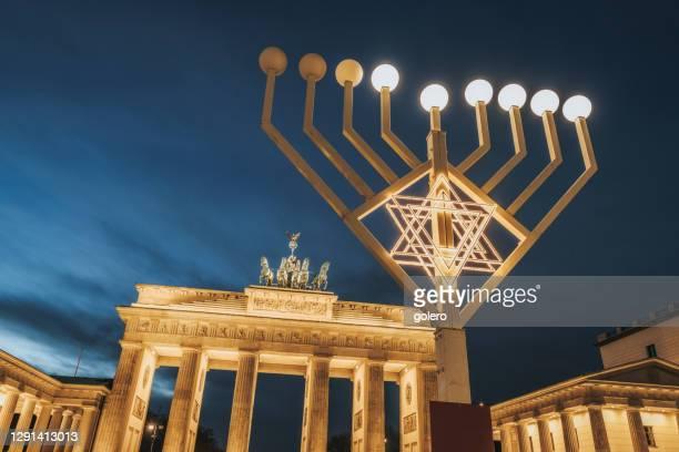 simbolo menorah illuminato davanti porta brandeburgo a berlino contro cielo ora blu - porta cittadina foto e immagini stock