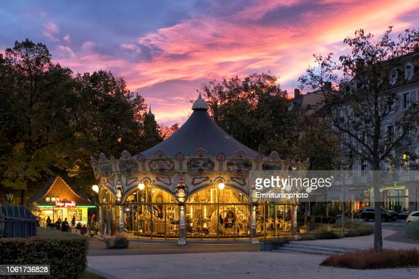 Illuminated merry-go- round in Colmar park with a dramatic sunset sky in the background.
