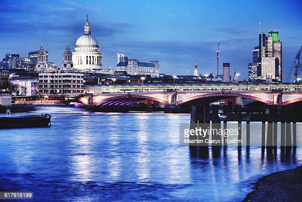 Illuminated Millennium Bridge Over Thames River By St Paul Cathedral At Dusk