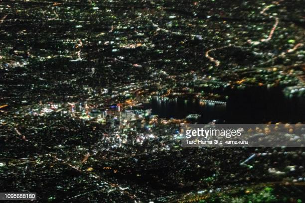 Illuminated Minato Mirai in Yokohama city in Kanagawa prefecture in Japan night time aerial view from airplane