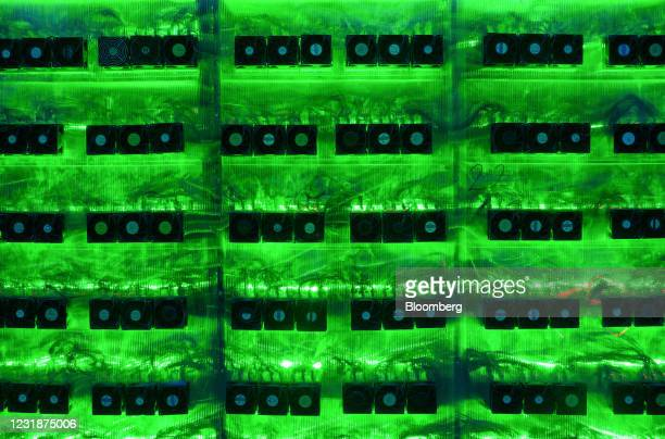 Illuminated mining rigs operate inside racks at the CryptoUniverse cryptocurrency mining farm in Nadvoitsy, Russia, on Thursday, March 18, 2021. The...