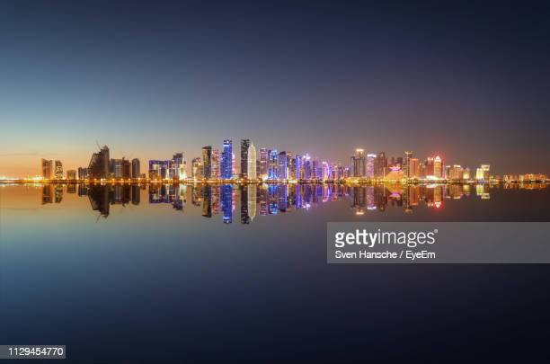 illuminated modern buildings by river against sky at night - doha photos et images de collection