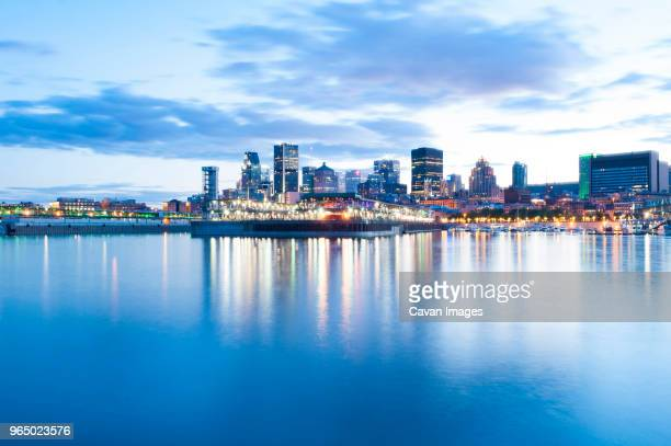 illuminated modern buildings by saint lawrence river against sky during sunset - river st lawrence stock pictures, royalty-free photos & images