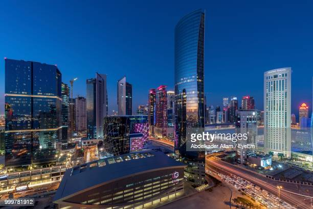 illuminated modern buildings in city against clear blue sky - qatar fotografías e imágenes de stock
