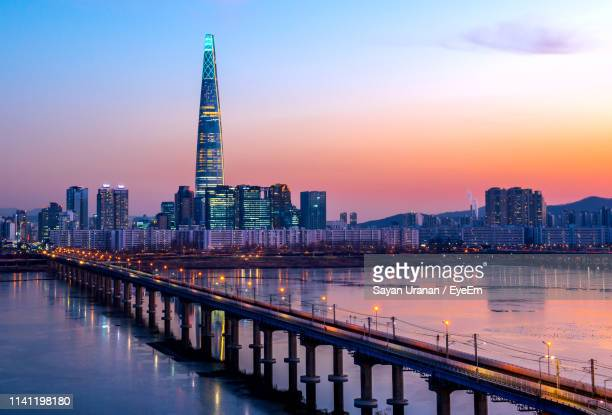illuminated modern buildings in city against sky during sunset - seoul stock pictures, royalty-free photos & images