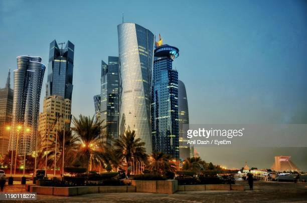 illuminated modern buildings in city against sky - pole stock pictures, royalty-free photos & images