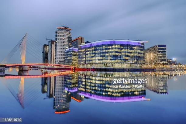 illuminated modern buildings in city at waterfront - manchester uk stock photos and pictures