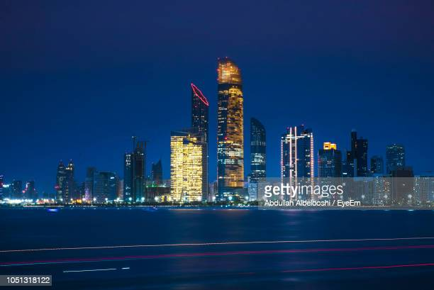 illuminated modern buildings in city by river at night - abu dhabi stock pictures, royalty-free photos & images