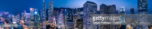 illuminated modern high rises in hong kong financial district against sky at blur hour - hong kong stock pictures, royalty-free photos & images
