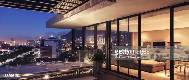 Illuminated modern living room and patio overlooking city