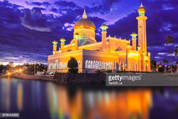 illuminated mosque by lake at night, brunei - brunei stock pictures, royalty-free photos & images