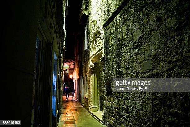 Illuminated Narrow Alley Amidst Buildings In City