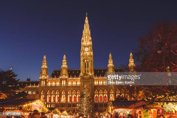 illuminated new town hall and christmas market against clear blue sky - town hall square stock pictures, royalty-free photos & images