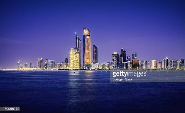 illuminated nighttime skyline of abu dhabi - abu dhabi stock pictures, royalty-free photos & images