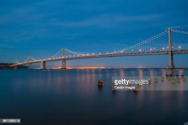 Illuminated Oakland Bay Bridge against blue sky at dusk