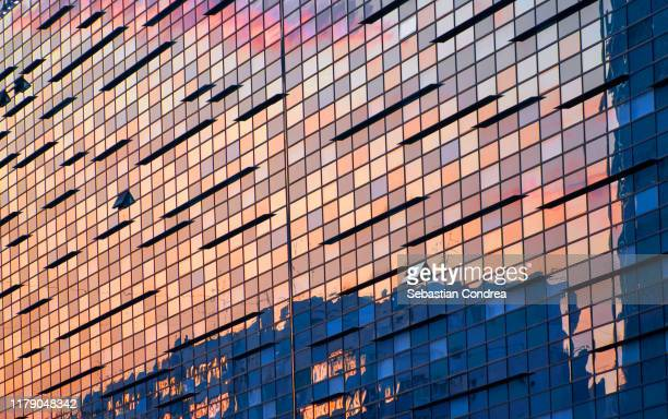 illuminated office building at sunset. bucuresti, romania. - wall building feature stock pictures, royalty-free photos & images