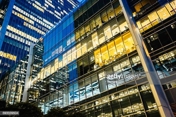 illuminated office buildings at canary wharf, london at night - illuminated stock pictures, royalty-free photos & images