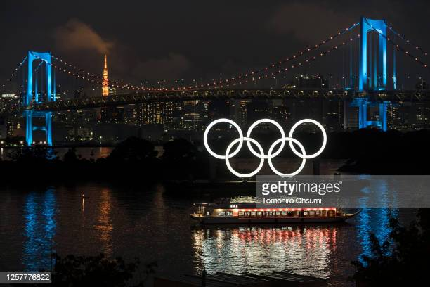 Illuminated Olympic rings are seen in front of the Rainbow Bridge and the Tokyo Tower at night on the day marking one year to go until the Tokyo...
