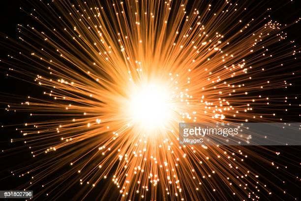 illuminated orange colored fiber optics radial pattern - detonate stock photos and pictures