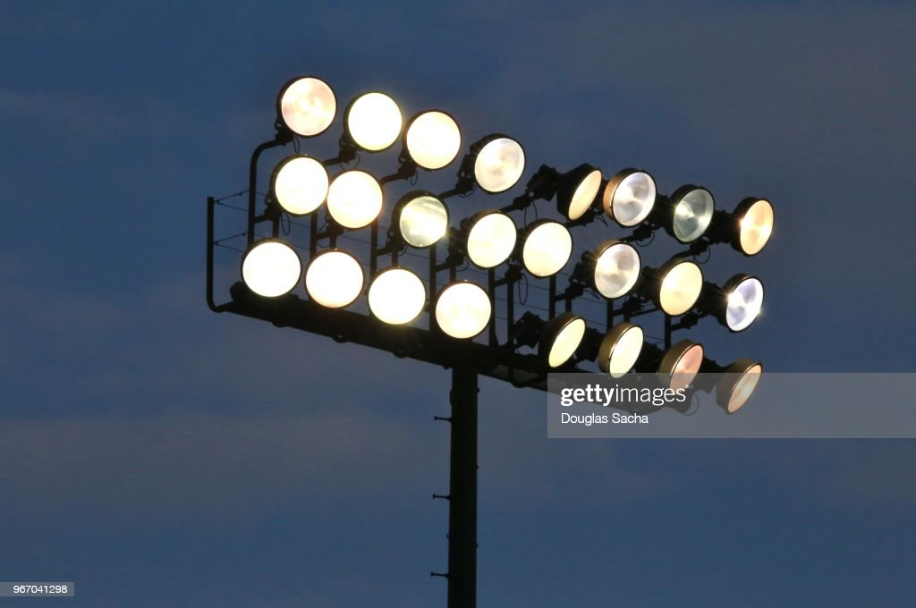 Illuminated overhead stadium scene lights : Stock Photo