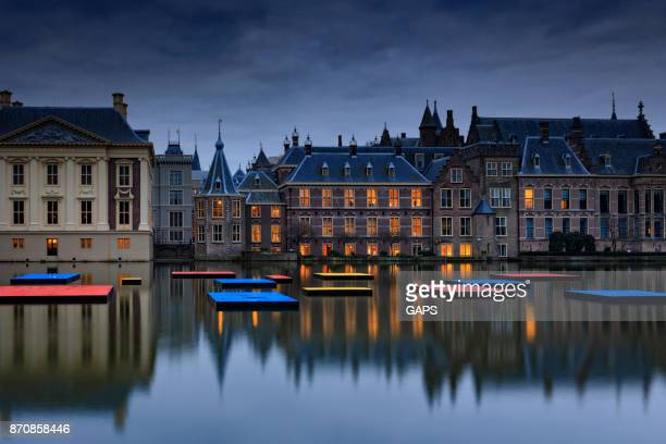 illuminated parliament buildings in the hague at dusk - the hague stock photos and pictures