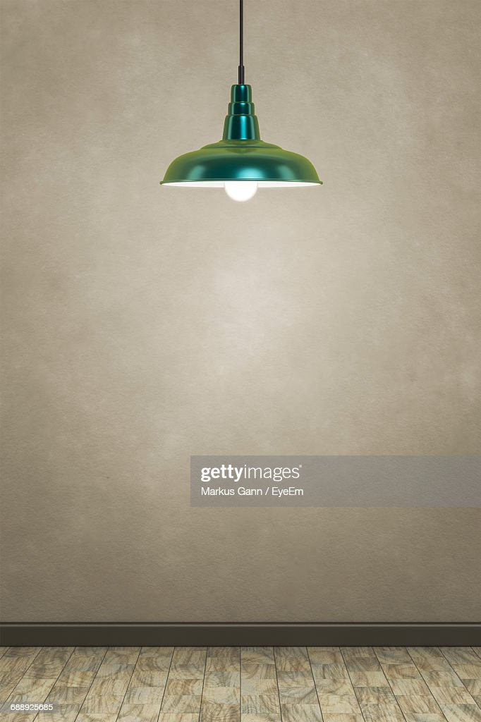 Illuminated Pendant Lamp Hanging Over Hardwood Floor By Wall : Stock Photo