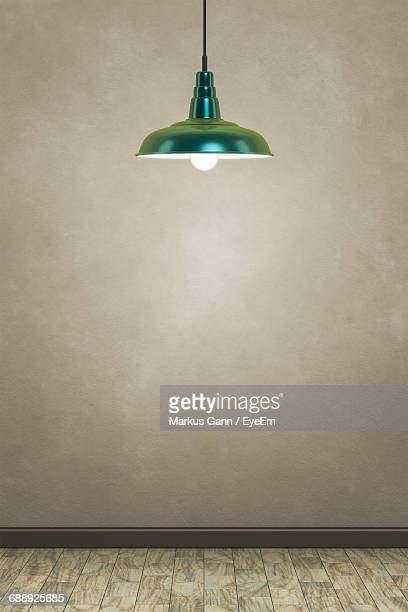 illuminated pendant lamp hanging over hardwood floor by wall - electric lamp stock pictures, royalty-free photos & images