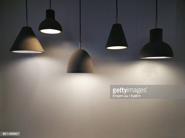 illuminated pendant lights against wall - pendant light stock pictures, royalty-free photos & images