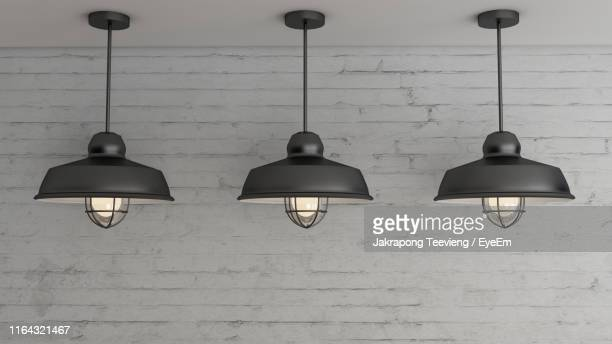 illuminated pendant lights hanging against brick wall - pendant light stock pictures, royalty-free photos & images