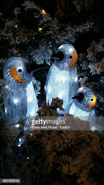 Illuminated Penguin Sculptures Amidst Frozen Trees During Christmas