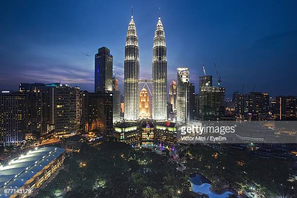 Illuminated Petronas Towers Amidst Buildings In City