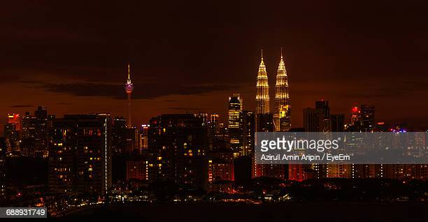 Illuminated Petronas Towers And Menara Kuala Lumpur Tower Amidst Buildings At Night