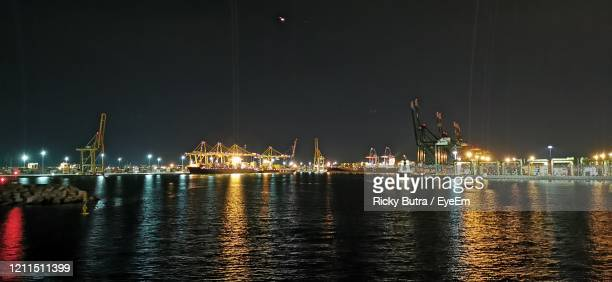 illuminated pier at harbor against sky at night - antwerpen stad stockfoto's en -beelden