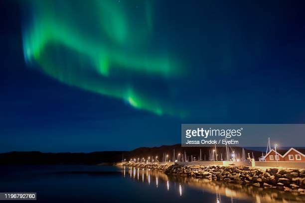 illuminated pier by sea against sky at night - jessa stock pictures, royalty-free photos & images
