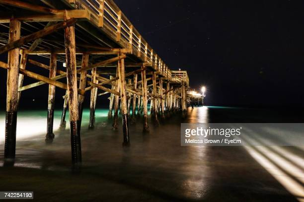illuminated pier over sea against sky at night - costa mesa stock photos and pictures