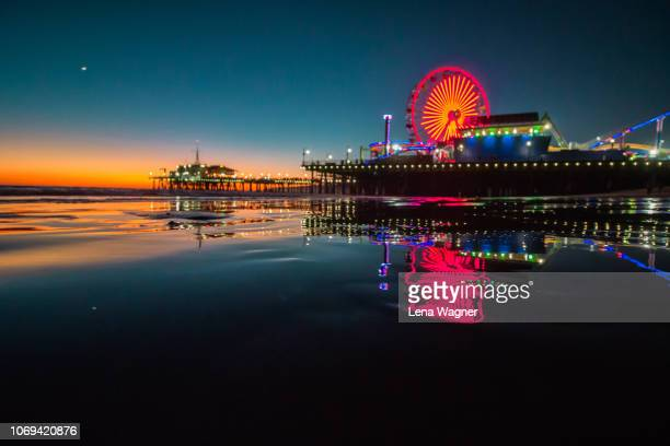 illuminated pier reflection after sunset - santa monica stock-fotos und bilder