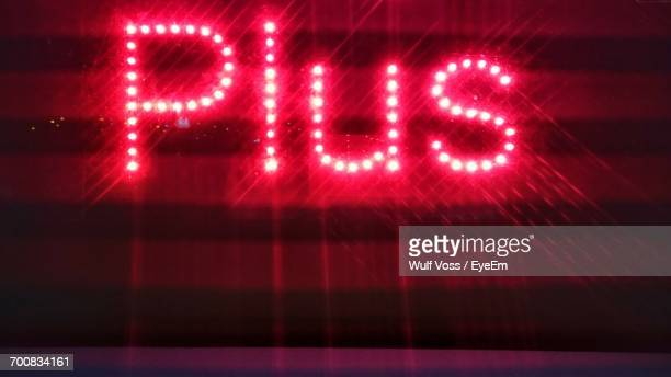 illuminated plus text on red wall - plus key stock photos and pictures