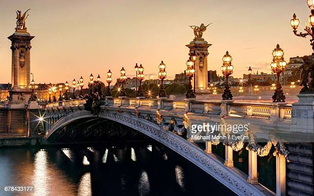 illuminated pont alexandre iii over seine river against clear sky - pont alexandre iii photos et images de collection