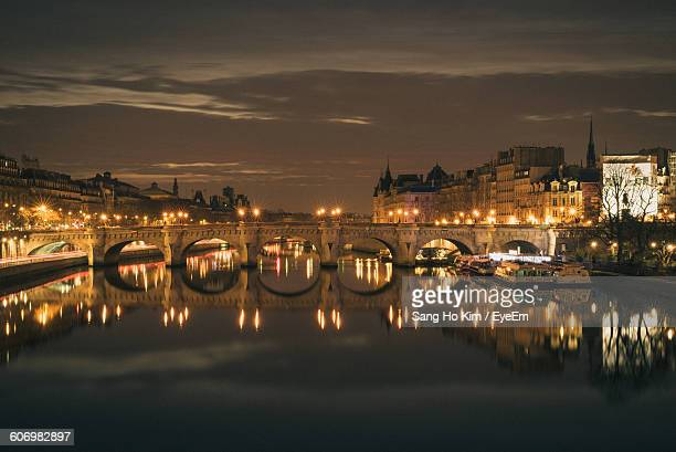 illuminated pont neuf over seine river amidst buildings against sky at night - pont neuf stock-fotos und bilder