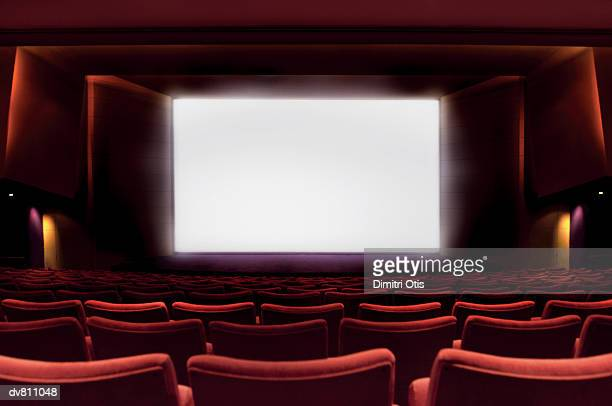 illuminated projection screen in an empty cinema - industria cinematografica foto e immagini stock