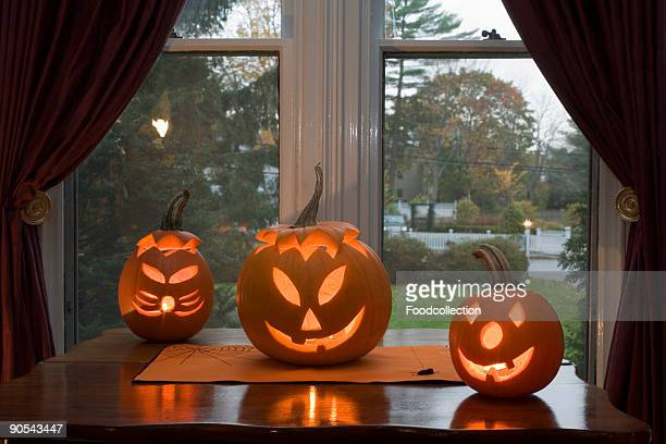 Illuminated pumpkin lanterns on window sill