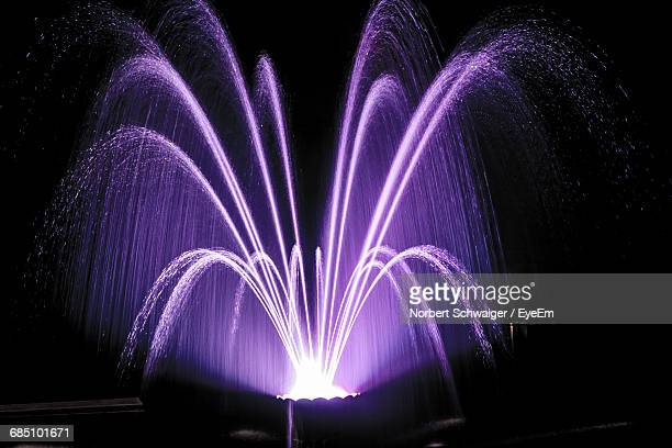 illuminated purple fountain at night - fountain stock pictures, royalty-free photos & images