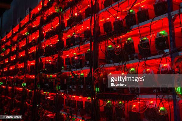 Illuminated racks of application-specific integrated circuit mining devices and power units at the BitCluster cryptocurrency mining farm in Norilsk,...
