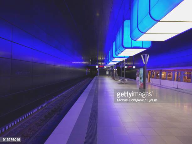 illuminated railroad station platform at night - bahnhof stock-fotos und bilder