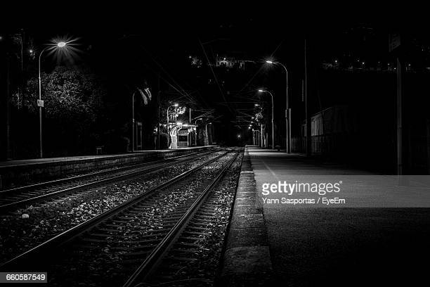 Illuminated Railroad Tracks At Night