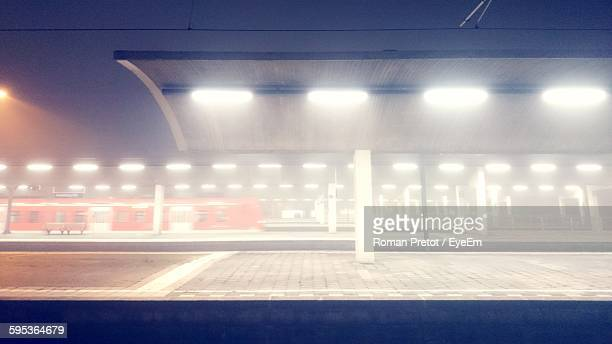 illuminated railway station at night - roman pretot stock-fotos und bilder