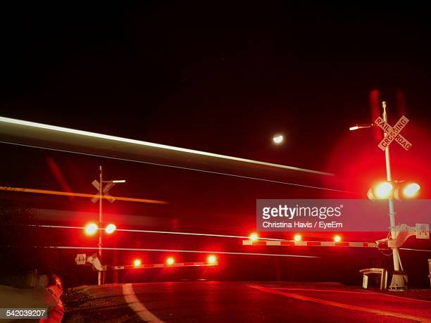 illuminated red crossing lights against train at night - railroad crossing stock pictures, royalty-free photos & images