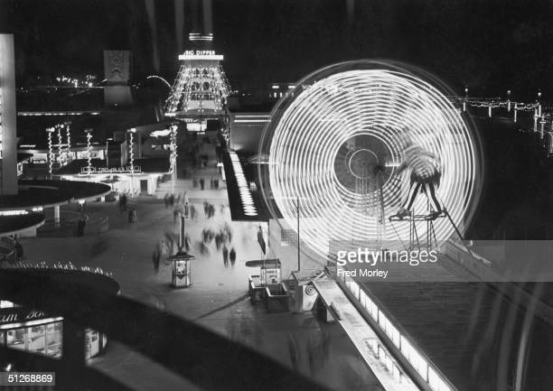 Illuminated rides at The Pleasure Beach in Blackpool, including a ferris wheel and the Big Dipper, 10th September 1955.