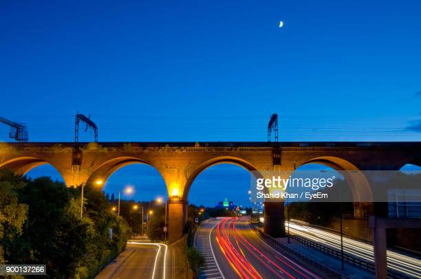 illuminated road against clear blue sky at night - stockport stock-fotos und bilder