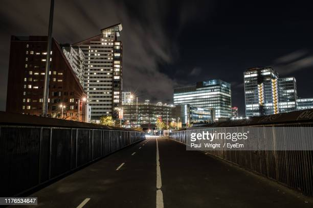 illuminated road amidst buildings in city against sky at night - night stock pictures, royalty-free photos & images